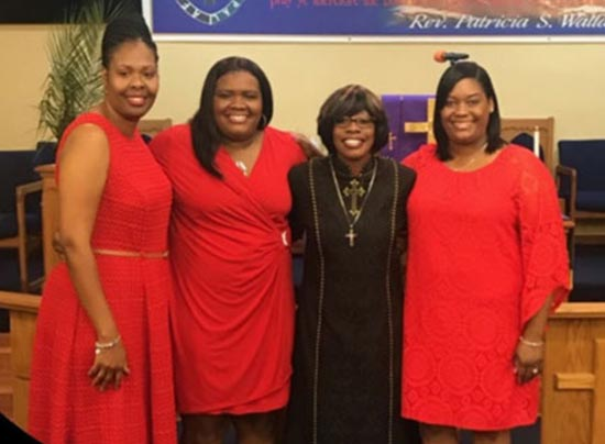 three women dressed in red and one in black standing and smiling for a photo