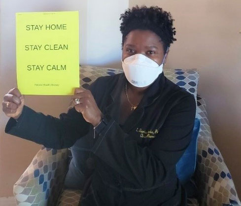 woman wearing protective face mask holding up a yellow sign asking people to stay home, stay clean, and stay calm