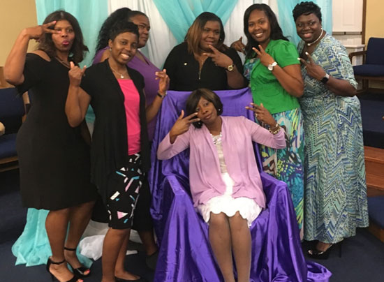 group of women smiling and holding up the peace sign for a photo