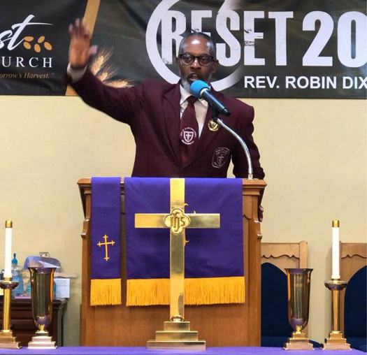 preacher with arm raised speaking into a microphone at a lectern