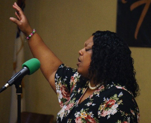 woman raising her hand and singing